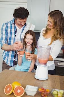 Souriant famille portant un jus de fruit