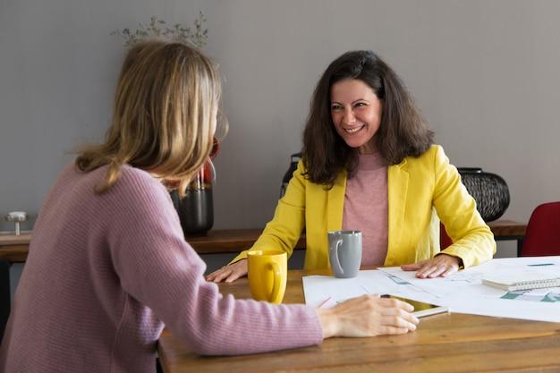 Souriant femme architecte parle avec un collègue