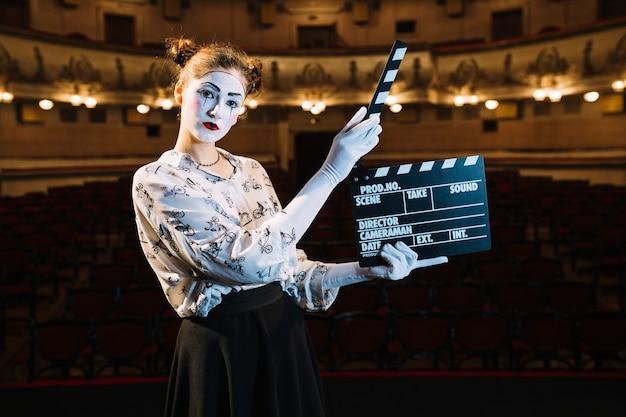 Souriant femme mime artiste tenant clap sur scène