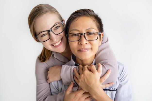 Souriant femmes multiethniques embrassant et regardant la caméra