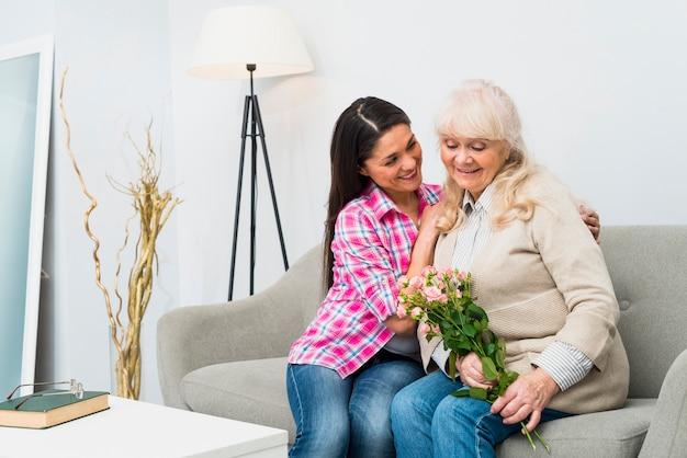 Souriant fille consolant sa mère âgée assise sur un canapé tenant des roses