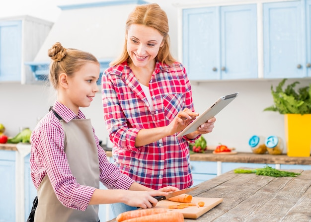 Souriant fille en regardant sa mère montrant la recette sur téléphone mobile