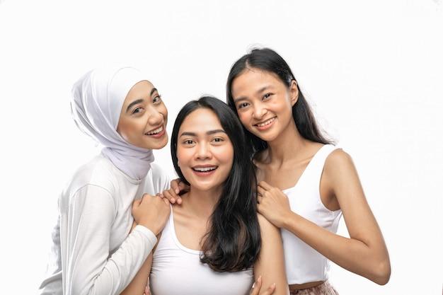 Souriant une fille voilée et deux jeunes filles asiatiques se tiennent l'une à côté de l'autre