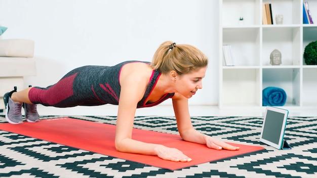 Souriant fit femme faisant la planche en regardant tablette numérique sur tapis rouge à la maison dans le salon