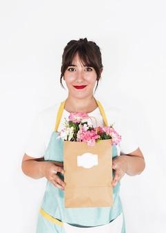 Souriant fleuriste femme tenant un sac en papier plein de fleurs fraîches