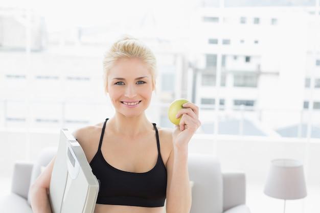 Souriant forme femme tenant la balance et apple dans le studio de remise en forme