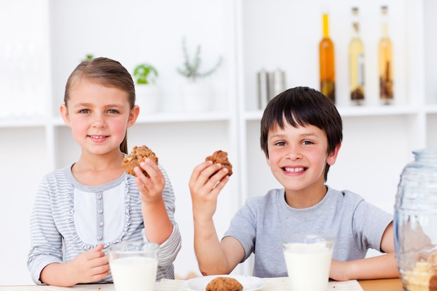 Souriant, frère et soeur, manger des biscuits et boire du lait