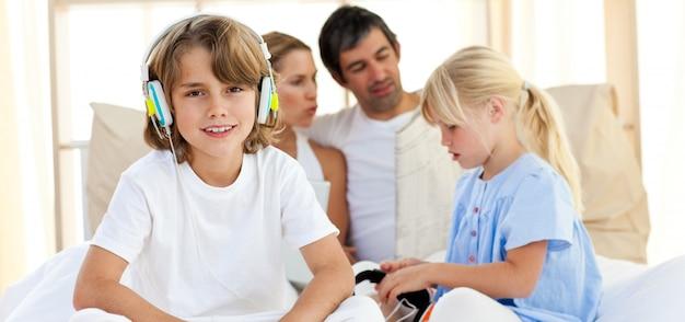 Souriant frères et sœurs écoute de la musique avec des écouteurs