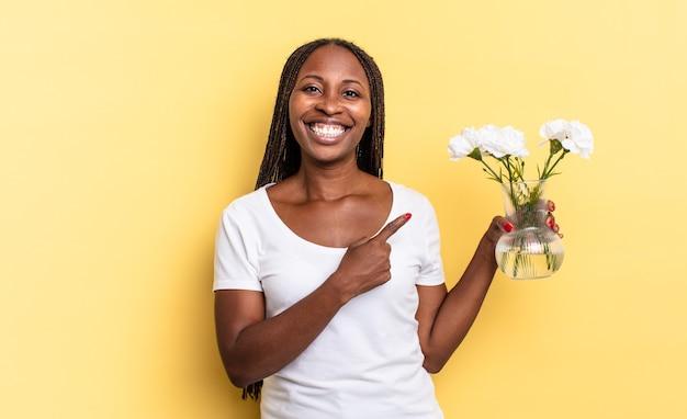 Souriant gaiement, se sentant heureux et pointant vers le côté et vers le haut, montrant l'objet dans l'espace de copie. concept de fleurs décoratives