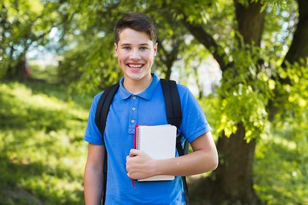 Souriant garçon adolescent avec des ordinateurs portables