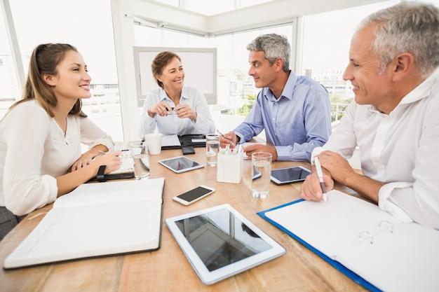 Souriant des gens d'affaires ayant une réunion