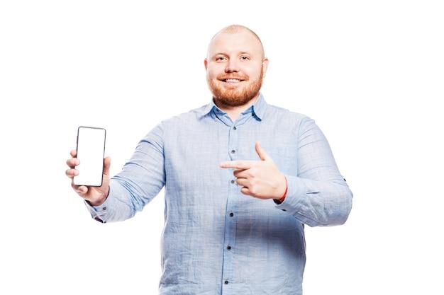 Souriant gros jeune homme rousse avec une barbe dans une chemise bleue avec un téléphone à la main. montre un doigt sur un écran isolé.