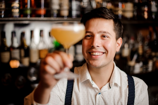 Souriant gros plan barman avec cocktail