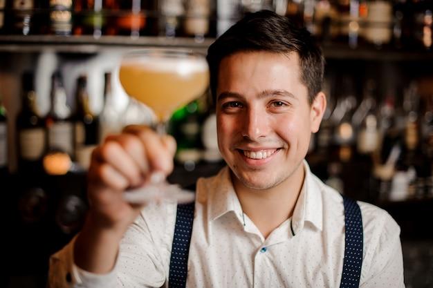 Souriant gros plan barman avec le cocktail