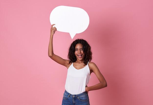 Souriant heureuse femme africaine tenant une bulle de dialogue vide