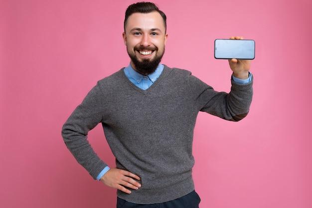 Souriant heureux beau heureux cool jeune brune homme mal rasé avec un pull gris élégant barbu
