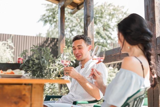 Souriant heureux jeune couple profitant du vin dans le jardin
