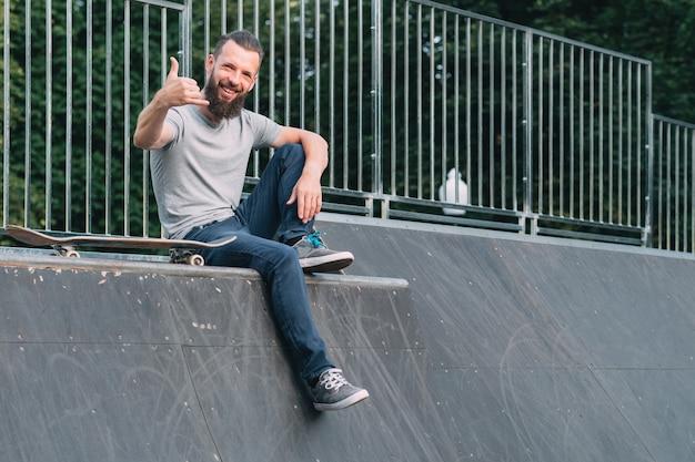Souriant hipster barbu assis sur la rampe et montrant le signe de shaka.