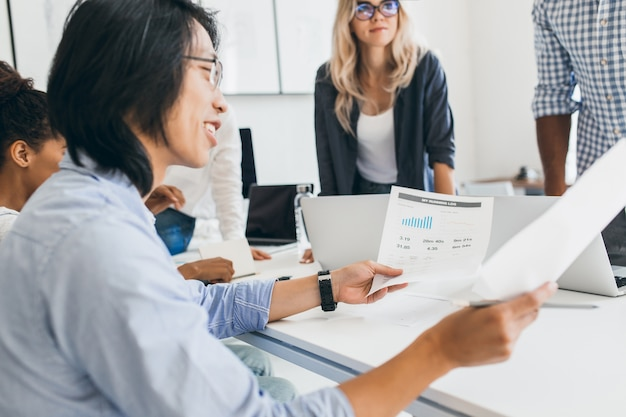 Souriant homme d'affaires asiatique analysant l'infographie dans son bureau. portrait en intérieur de jeunes spécialistes en informatique avec un développeur chinois à lunettes