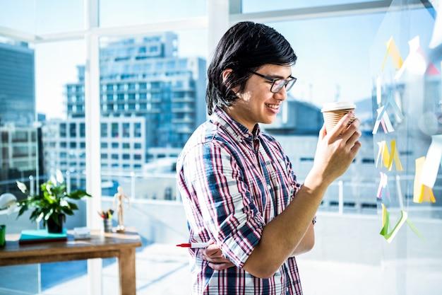 Souriant homme d'affaires créatif avec un café à emporter au bureau