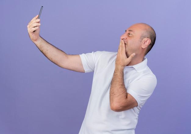 Souriant homme d'affaires mature occasionnel mettant la main sur la bouche et prenant selfie isolé sur fond violet