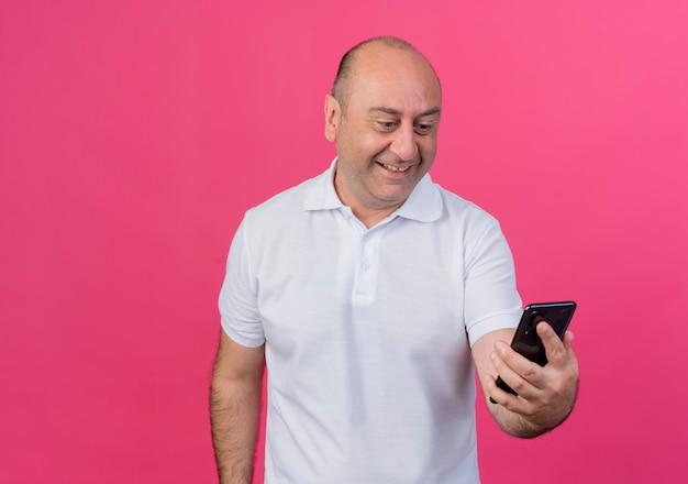 Souriant homme d'affaires mature occasionnel tenant et regardant le téléphone mobile isolé sur fond rose avec espace de copie