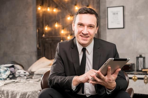 Souriant homme d'affaires travaillant sur une tablette