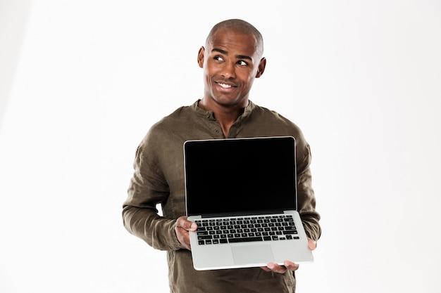 Souriant homme africain pensif montrant un écran d'ordinateur portable vierge et levant