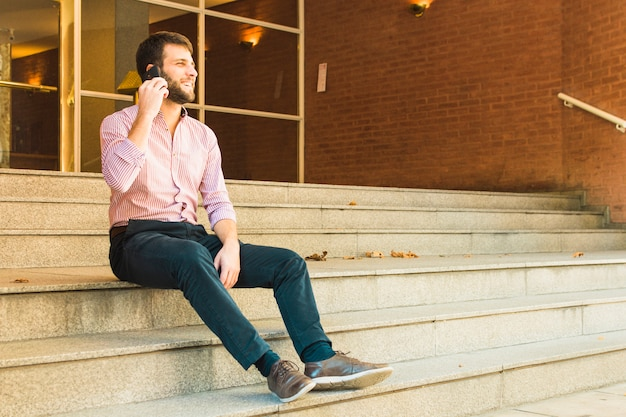 Souriant homme assis sur un escalier parlant au téléphone mobile