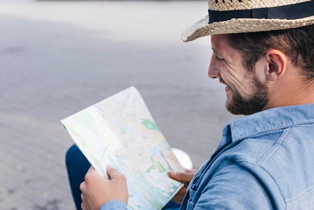 Souriant homme barbu portant chapeau lecture carte à l'extérieur