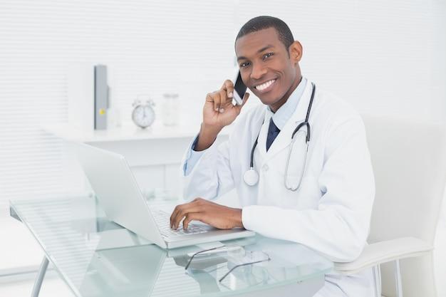 Souriant homme médecin utilisant un téléphone portable et un ordinateur portable