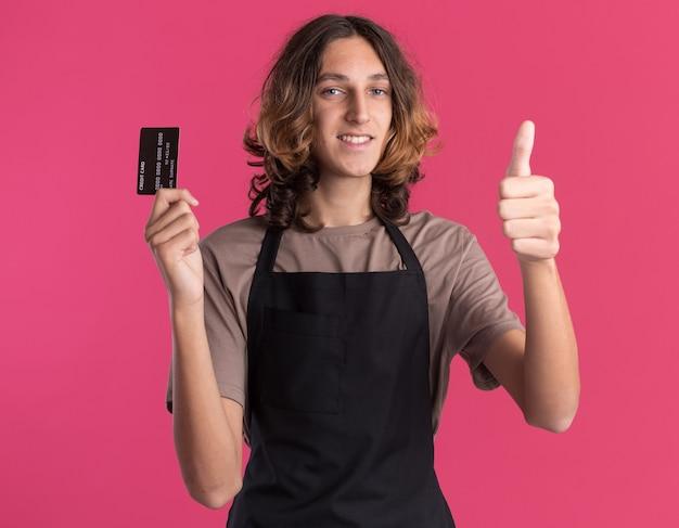 Souriant jeune beau barbier en uniforme montrant la carte de crédit et le pouce vers le haut