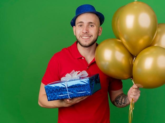 Souriant jeune beau mec de fête slave portant chapeau de fête tenant des ballons et un coffret cadeau regardant la caméra isolée sur fond vert avec espace de copie