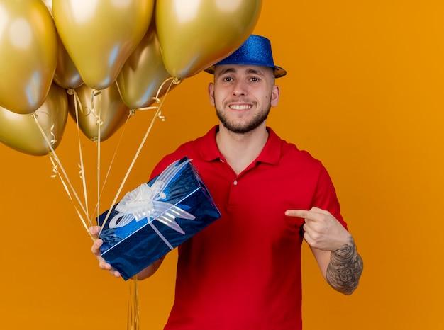 Souriant jeune beau mec de fête slave portant chapeau de fête tenant des ballons et un coffret cadeau regardant la caméra pointant vers un coffret cadeau isolé sur fond orange