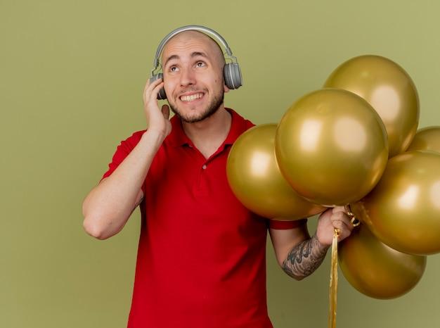 Souriant jeune beau mec de fête slave portant des écouteurs tenant des ballons touchant des écouteurs en levant isolé sur fond vert olive