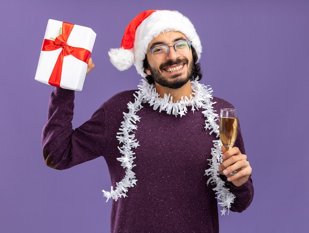 Souriant jeune beau mec portant chapeau de noël avec guirlande sur le cou tenant la boîte-cadeau avec verre de champagne isolé sur fond bleu