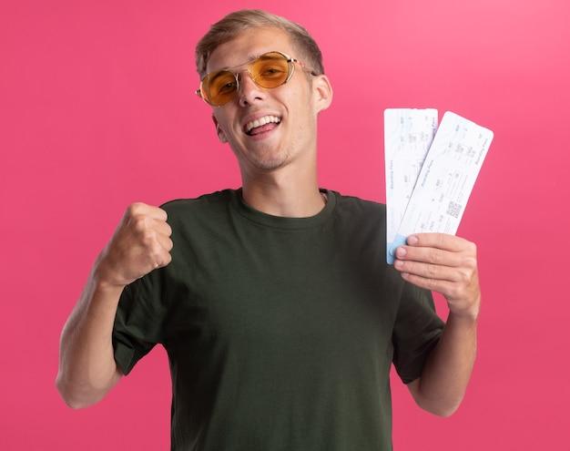Souriant jeune beau mec portant chemise verte et lunettes tenant des billets montrant oui geste isolé sur mur rose