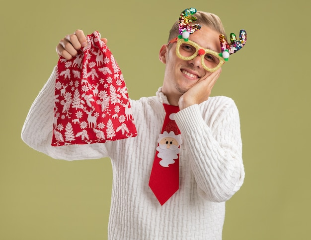 Souriant jeune beau mec portant des lunettes de nouveauté de noël et cravate de père noël tenant le sac de noël regardant la caméra en gardant la main sur le visage isolé sur fond vert olive