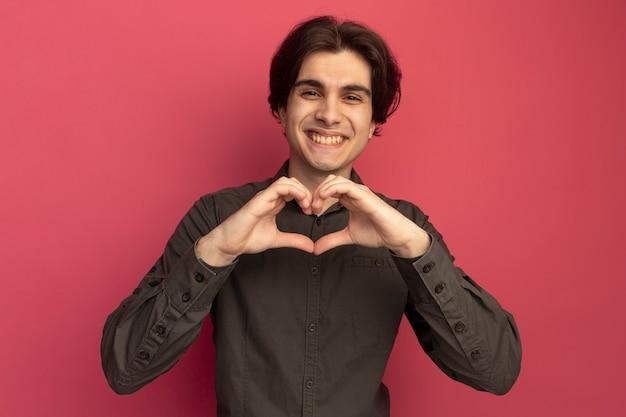 Souriant jeune beau mec portant un t-shirt noir montrant un geste cardiaque isolé sur un mur rose