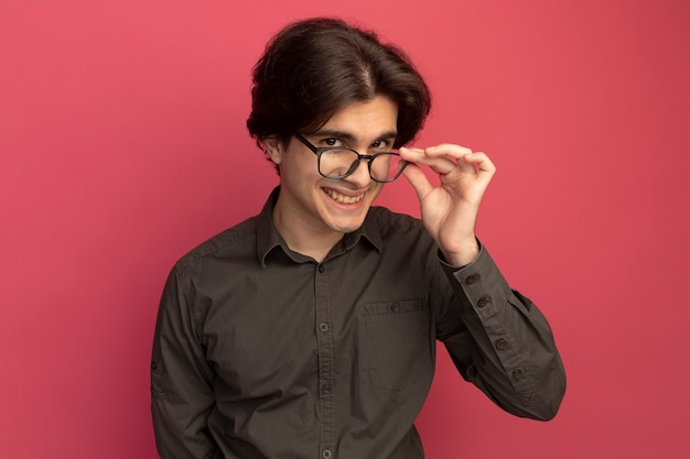 Souriant jeune beau mec portant un t-shirt noir portant et tenant des lunettes isolées sur un mur rose