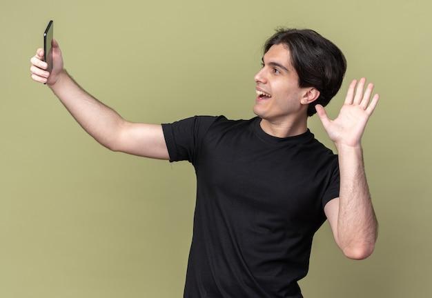 Souriant jeune beau mec portant un t-shirt noir prendre un selfie montrant bonjour geste isolé sur mur vert olive