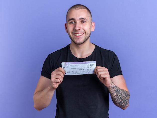 Souriant jeune beau mec portant un t-shirt noir tenant un billet isolé sur un mur bleu