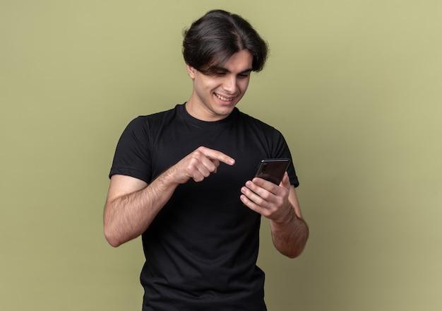 Souriant jeune beau mec portant un t-shirt noir tenant et composer le numéro sur téléphone isolé sur mur vert olive