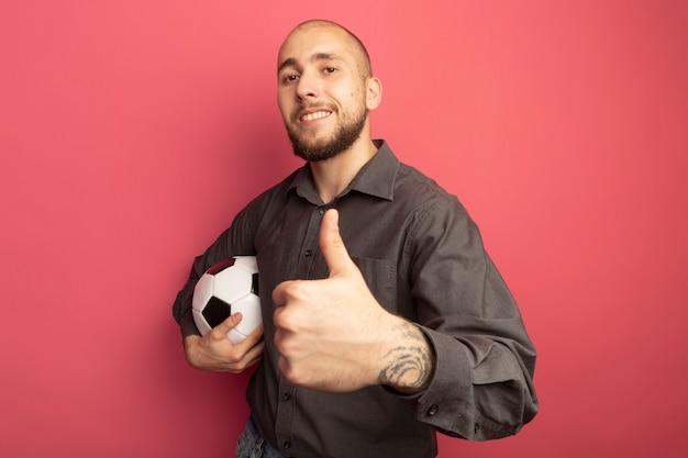 Souriant jeune beau mec tenant le ballon et montrant le pouce vers le haut