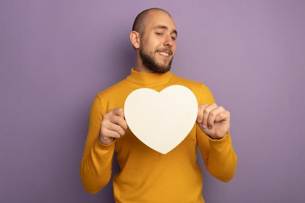 Souriant jeune beau mec tenant une boîte en forme de coeur isolé sur violet