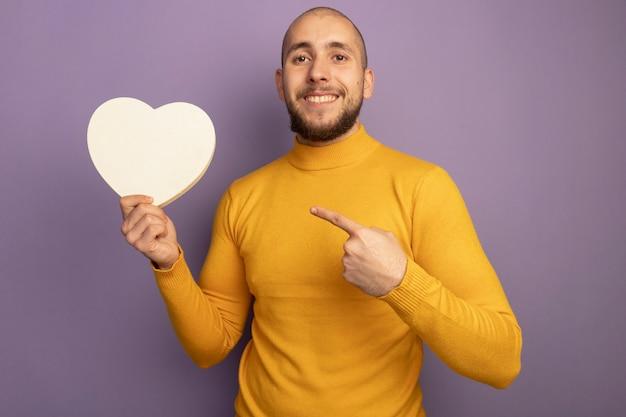 Souriant jeune beau mec tenant et pointe la boîte en forme de coeur isolée sur le mur violet