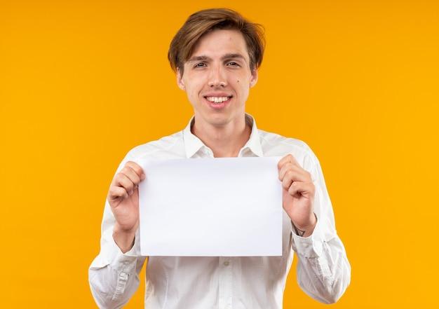 Souriant jeune beau mec vêtu d'une chemise blanche tenant du papier blanc isolé sur un mur orange