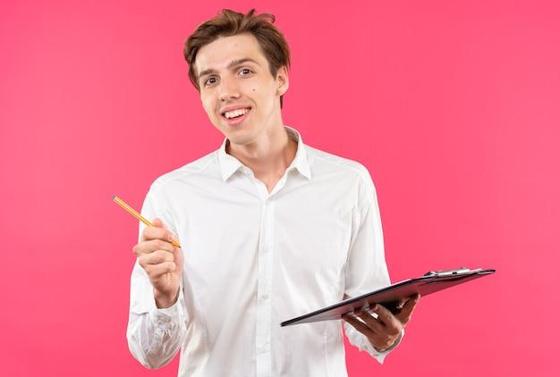 Souriant jeune beau mec vêtu d'une chemise blanche tenant un presse-papiers avec un stylo isolé sur un mur rose