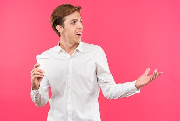 Souriant jeune beau mec vêtu d'une chemise blanche tenant une tasse de points de café avec la main sur le côté isolé sur un mur rose