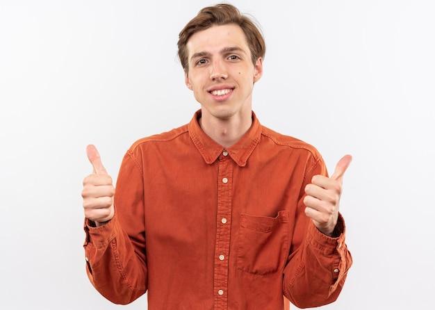 Souriant jeune beau mec vêtu d'une chemise rouge montrant les pouces vers le haut isolé sur mur blanc